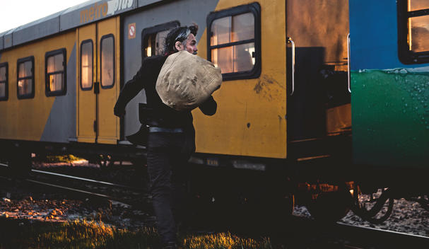 cool beaded man walking by a train track with a sack on his back