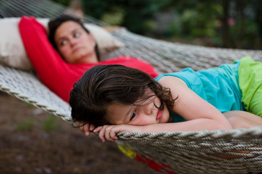 A Mother And Daughter Relax In A Hammock Together