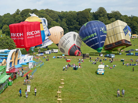 Spectators watch as hot-air balloons are inflated ready to participate in a flight during the Bristol International Balloon Festival.