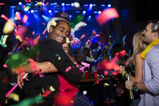 Confetti falling hugging couple enjoying New Year celebration