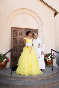 Hispanic priest and girl celebrating quinceanera outside Catholic church
