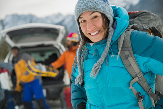 Portrait of woman with friends preparing for winter hike in mountains