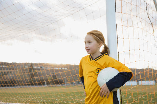 Player with soccer ball leaning against goal post