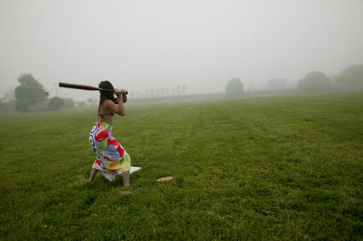Girl Holding Baseball Bat In Misty Landscape