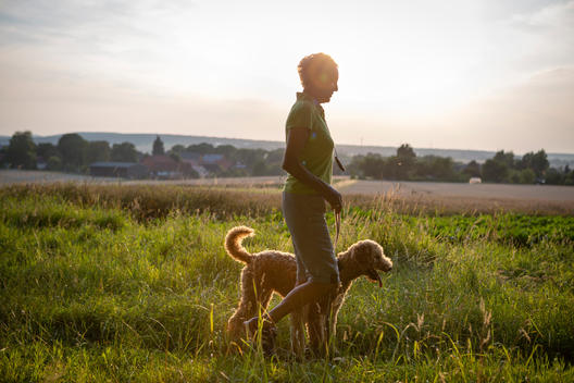 Senior woman walking with her dog over a meadow