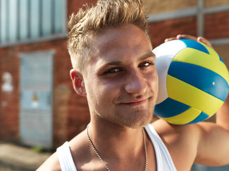Germany, Duesseldorf, Young man with volley ball in industrial area, smiling, portrait