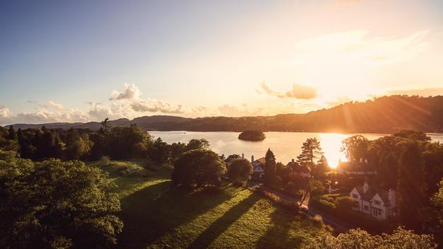 Wonderful view of Lake Windermere in the Lake District with bright sunset, light and mountains in the background.