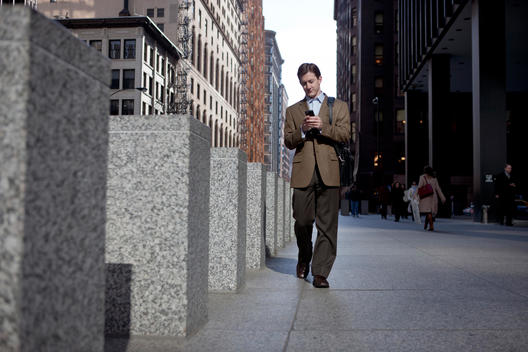 A Business Man Walks While Checking His Cell Phone In Downtown Chicago.