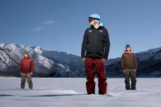Three Young People Laughing Standing In Snow ,Mountains In The Background