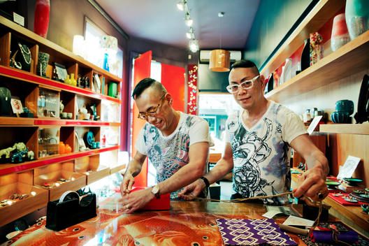 Two men in glasses inside their oriental store
