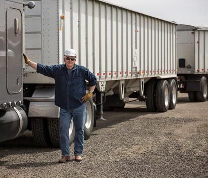 Caucasian trucker standing by semi-truck