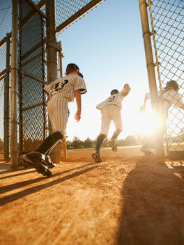 Baseball players (10-11) entering baseball diamond
