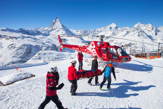 Rescue personnel are carrying an injured skier to a helicopter of Air Zermatt at the Gornergrat ski area in Zermatt, Switzerland. The famous Matterhorn mountain is in the background.