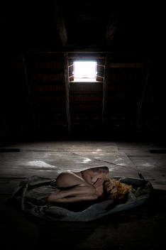 Nude woman on attic with window in back.