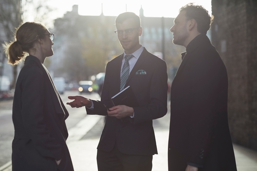 Business colleagues standing in street holding diary talking