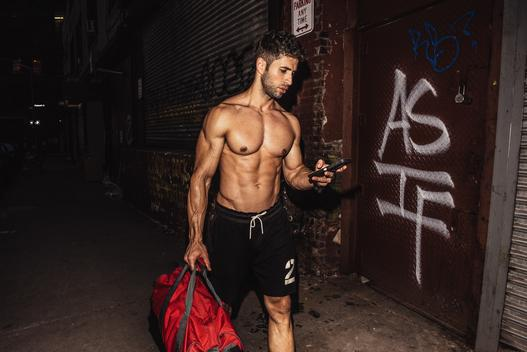 Bare chested young man reading smartphone text on street at night