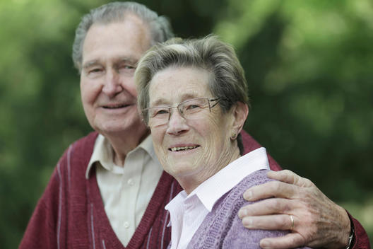 Germany, Cologne, Portrait of senior couple in park, smiling