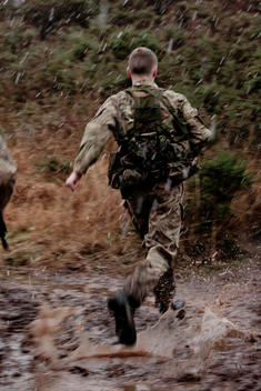 solo soldier running away from camera in poor weather