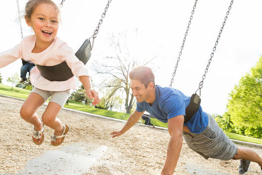 Father playing with daughter on swing
