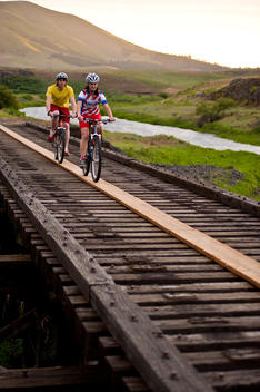 Young couple crossing a trestle bridge while mountain biking the Klickitat trail.