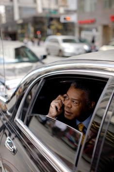 A Business Man Looks Out The Window Of A Corporate Car While Talking On His Cell Phone.