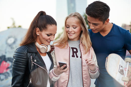 three young people chatting in urban location