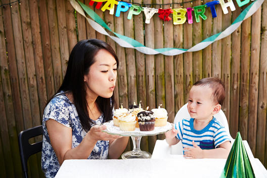 Mother blowing out candles on baby boy\'s birthday cakes
