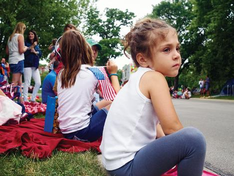 Girl sitting on curb waiting for the fourth of July parade.