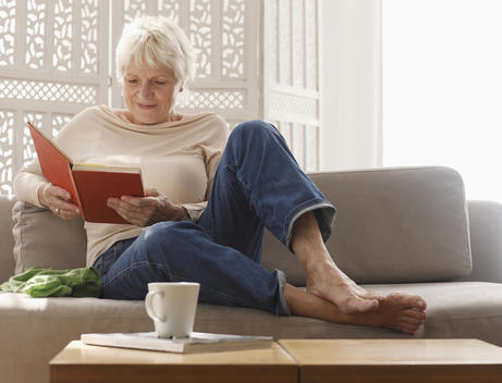 Senior Woman Relaxing On Sofa With Book
