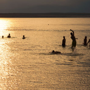 Silhouette Of Young People Playing In The Sea In Sunset