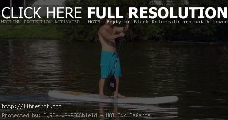 Man Stands at Paddle Board