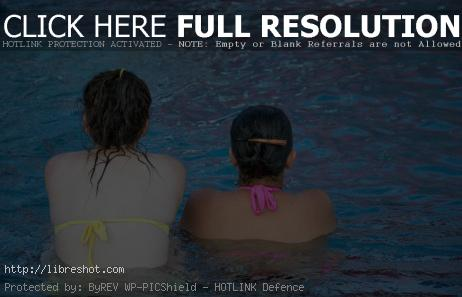 Free image of Two women sitting in a swimming pool