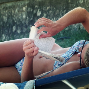 Girl Reading A Book On The Beach