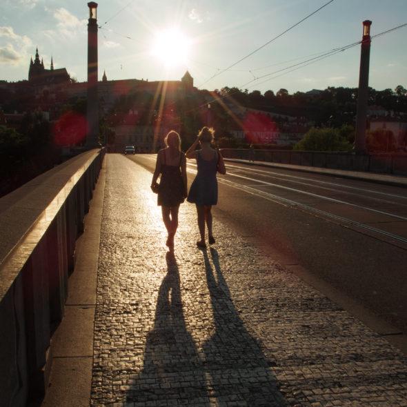 Two tourists – girls walking on the Prague bridge