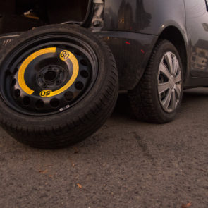 The spare tire leaning against a black car