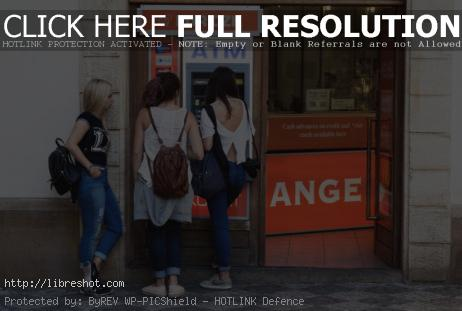 Free image of Three young women and ATM