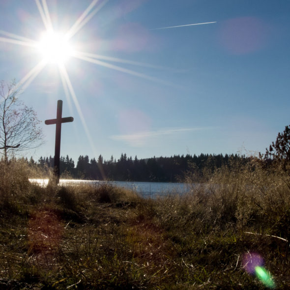 Sun over the lake and a crucifix