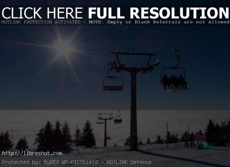 Free image of A chair lift at the top of a mountain on a sunny day