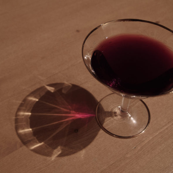 Glass of red wine on a wooden table